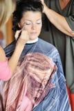 Beautiful bride applying wedding make-up by make-up artist Stock Photography