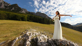 Beautiful bride with arms up in nature royalty free stock photography