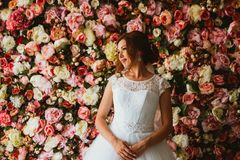 Beautiful bride on the background of a wall of flowers.  Stock Image
