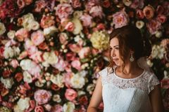 Beautiful bride on the background of a wall of flowers.  Royalty Free Stock Images