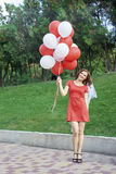 Beautiful bride with balloons in the park Royalty Free Stock Photography