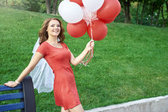 Beautiful bride with balloons in the park Stock Image