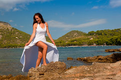 Beautiful bride on the beach. Beautiful bride posing in white dress on the Formentor beach in Mallorca Stock Photo
