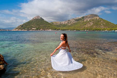 Beautiful bride on the beach. Beautiful bride posing in white dress on the Formentor beach in Mallorca Royalty Free Stock Photos