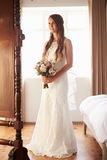 Beautiful Bride In Bedroom Looking at Mirror Stock Photography