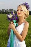 Beautiful bride blond blue eyes green field Stock Images