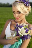 Beautiful bride blond blue eyes green field Royalty Free Stock Photos