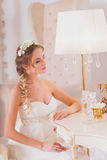 Beautiful bride blond girl in a wedding dress worn front of the mirror Stock Image