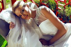 Beautiful bride with blond hair in wedding dress lying on sofa Royalty Free Stock Photos