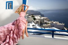 Beautiful bride blonde female model in amazing wedding dress poses on the island of Santorini Royalty Free Stock Photos