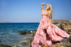 Beautiful bride blonde female model in amazing wedding dress poses on the island of Santorini Royalty Free Stock Photo