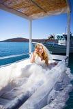 Beautiful bride blonde female model in amazing wedding dress poses on the island of Santorini Stock Photography