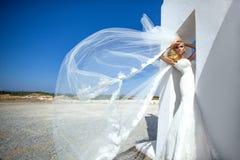 Beautiful bride blonde female model in amazing wedding dress poses on the island of Santorini Royalty Free Stock Images