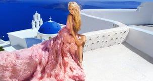 Beautiful bride blonde female model in amazing wedding dress poses on the island of Santorini Royalty Free Stock Photography