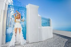 Beautiful bride blonde female model in amazing wedding dress poses on the island of Santorini in Greece Stock Image