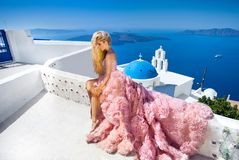 Beautiful bride blonde female model in amazing wedding dress poses on the island of Santorini in Greece Royalty Free Stock Photo