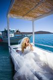 Beautiful bride blonde female model in amazing wedding dress poses on the island of Santorini in Greece Stock Photography