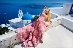 Beautiful bride blonde female model in amazing wedding dress poses on the island of Santorini in Greece Royalty Free Stock Images