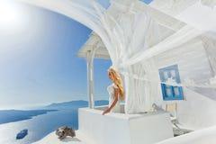 Beautiful bride blonde female model in amazing wedding dress poses on the island of Santorini Royalty Free Stock Image