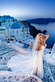 Beautiful bride blonde female model in amazing wedding dress poses on the island of Santorini Stock Photo