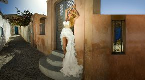 Beautiful bride blonde female model in amazing wedding dress poses on the island of Santorini in Greece and beyond. It is a beautiful view royalty free stock photography