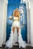 Beautiful bride blonde female model in amazing wedding dress poses on the island of Santorini Stock Images