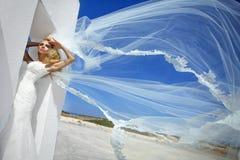Beautiful bride blonde female model in amazing wedding dress poses on the island of Santorini Stock Photos