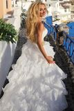 Beautiful bride, blonde model in amazing wedding dress runs to Santorini in Greece. Royalty Free Stock Image