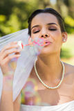 Beautiful bride blowing soap bubbles in park Royalty Free Stock Image