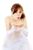 Beautiful bride blows at the hands of Stock Photos