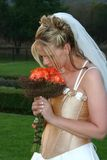 Beautiful bride with bouquet. Beautiful blonde bride holding her bouquet and smelling the roses Stock Images