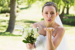 Beautiful bride with bouquet blowing kiss in garden Royalty Free Stock Photos