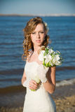 Beautiful bride with a bouquet of calla lilies on coast of river Royalty Free Stock Photos