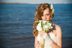 Beautiful bride with a bouquet of calla lilies on coast of river Stock Images