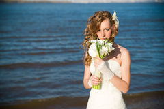 Beautiful bride with a bouquet of calla lilies on coast of river Stock Image