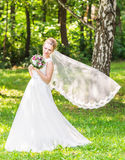 Beautiful bride with bouquet of flowers outdoor Stock Photo