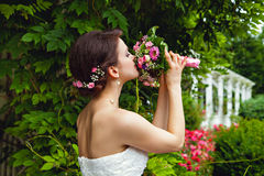 Beautiful bride with bouquet of flowers in park Stock Image