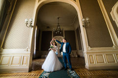 Beautiful bride with bouquet and handsome groom wearing blue suit dancing in arch at yellow walls background.  Royalty Free Stock Images