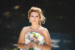 Beautiful Bride with Bouquet. Beautiful bride holding wedding bouquet in sunlight Royalty Free Stock Photo