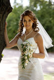 Beautiful bride. The beautiful bride with bouquet in park Stock Image