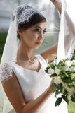 Beautiful bride. The beautiful bride with bouquet in park Royalty Free Stock Photo