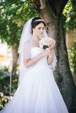 Beautiful bride with a bouquet in a park Royalty Free Stock Photography