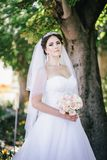 Beautiful bride with a bouquet in a park Stock Photo