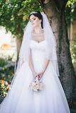Beautiful bride with a bouquet in a park Stock Photography