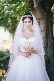 Beautiful bride with a bouquet in a park Stock Photos