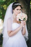 Beautiful bride with a bouquet in a park Stock Image