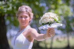 Beautiful bride with bouquet in park Stock Image