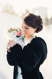 Beautiful bride with bouquet posing outdoor in snow Royalty Free Stock Images