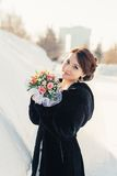 Beautiful bride with bouquet posing outdoor in snow Stock Photos