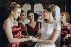 Lovely bride and bridesmaids next to the big window. Beautiful bride and bridesmaids posing near window, wedding preparation Royalty Free Stock Photos